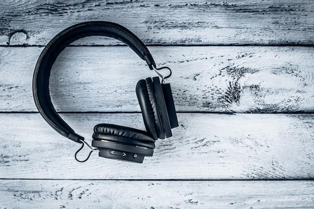灰色の木製の背景に黒のヘッドフォン。レイアウト、テキストスペース。音楽ライフスタイル。