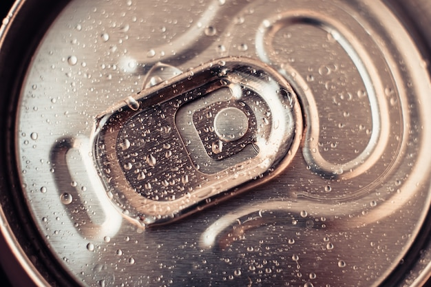 Металлический напиток можно с каплями воды. блестящее пиво можно крупным планом. золотая бутылка напитка, крышка упаковки колы. вид сверху.