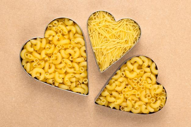 Сырые макароны на коричневой бумаге. сырые макароны в форме сердца. куча желтой лапши.