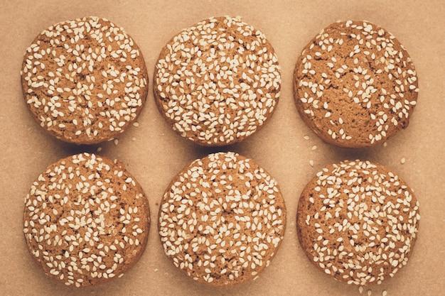 ベーキングペーパーにオートミールクッキー。ゴマの手作りパン屋さん。茶色の背景。ビスケットのグループ。