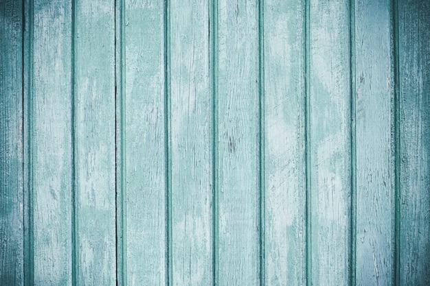 剥離ペイントで明るい色の木製フェンス。ぼろぼろの老朽化した木の板。ウッドラメラ。青いラフ塗装板の表面。抽象的な壁紙。ビンテージ背景。テクスチャ要素。