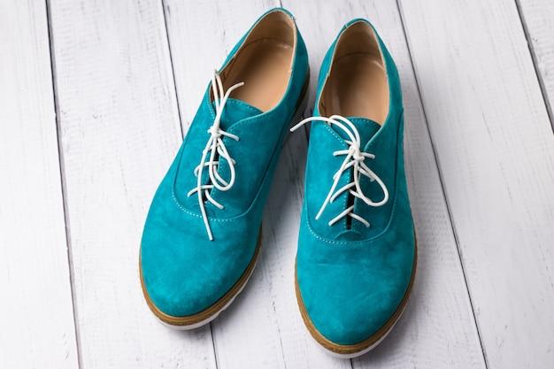 木製の背景にひもで緑のカジュアルなスエードの靴のペア。ターコイズブルーの女性のオックスフォード、オックスフォードの靴。
