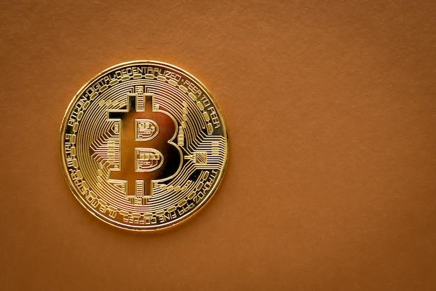 Один золотой биткойн на коричневой предпосылке. электронная коммерция, криптовалюта. блокчейн, международный майнинг.