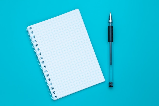 空白のノートブックと青の背景にペン。コピースペース。教育コンセプト。