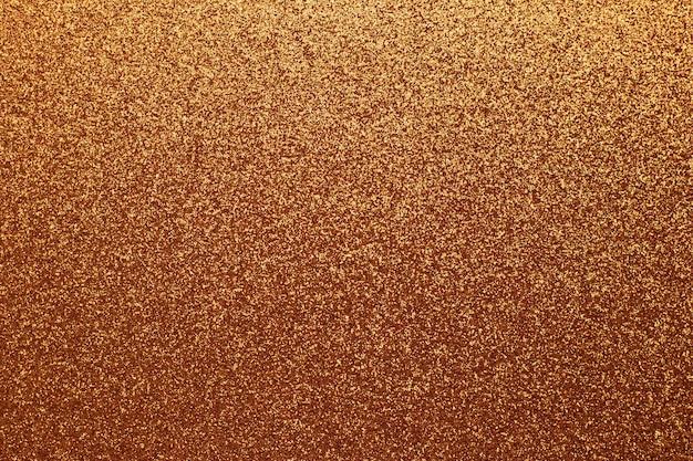 Золотой блестящий фон, желтые блестки, коричневая зернистая текстура. материал выкройки, металлическая мишура, отделка.