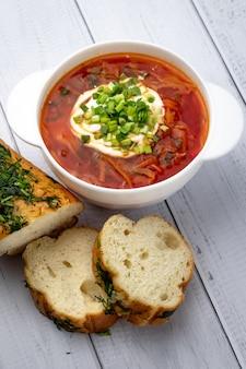 Русский красный борщ со сметаной и зеленью в белом шаре и кусках хлеба на деревянной предпосылке, таблице. концепция украинской кухни.