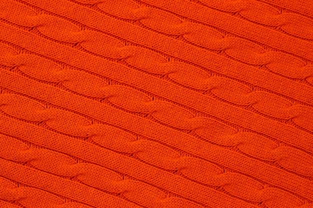 Абстрактный яркий оранжевый вязаный фон. узор пряжи, трикотажная поверхность, трикотажные обои. орнамент из акриловых кос. шерстяное плетение.