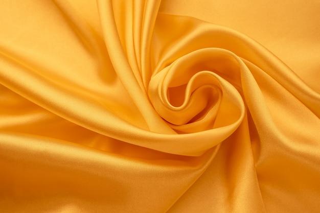 シルクの背景。黄色のサテンの折り目。滑らかな光沢のある生地の質感、抽象的な明るい壁紙。しわくちゃの繊維表面。
