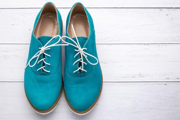 ターコイズのレースアップ女性靴、アクアカラーのスエードブーツ。白いウッドの背景に履物のペア。コピー、テキストスペース。上面図。カジュアルなファッションスタイルのコンセプト。