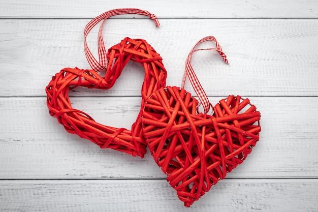 Два красных самодельных сердца с лентой на белом деревянном фоне. символ любви, романтический фон. праздничная подарочная карта на день святого валентина.