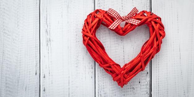 白い木製の背景、テキストスペースを持つテンプレートのリボンから赤いハート。愛の概念、バレンタインカード、モックアップとフラットレイアウト。レイアウト装飾。お祝いフレーム、アートバナー。バレンタインデー-休日。