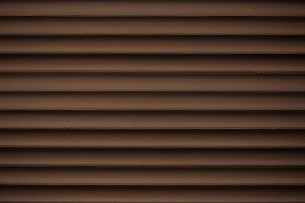 金属の縞模様。ダークブラウンのリブ付きサイディングの質感。フェンスのライン、抽象的な溝付き背景。