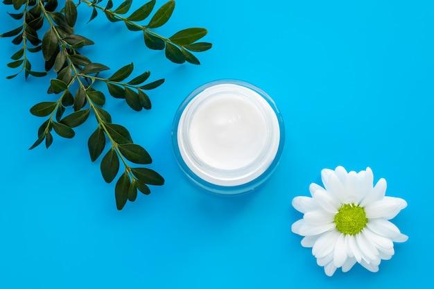 白いカモミールの花と青色の背景に緑の枝が付いている顔のクリーム瓶。ガラス容器に入ったハーブローション、自然化粧品。