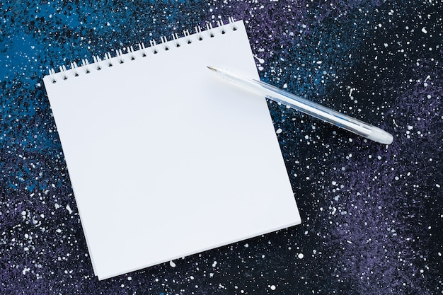 抽象的な暗い青色の背景にテキストをコピースペースを持つ空白のスパイラルノート。計画のコンセプト。ホワイトペーパーのページとペン、空のシート、モックアップ。