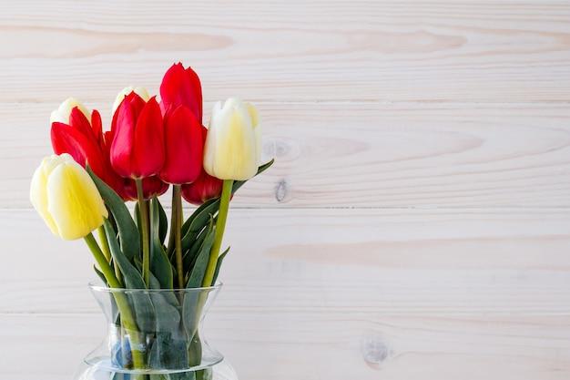 明るい木製の背景の上に花瓶のチューリップ。テキストスペース、花のフレームのギフトカード。