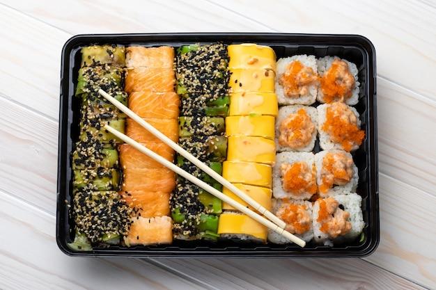 Набор суши роллы в черный лоток и деревянные палочки для еды.