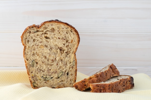 Запеченный хлеб с семенами на кухонное полотенце. деревянный стол. ломтики черного хлеба.