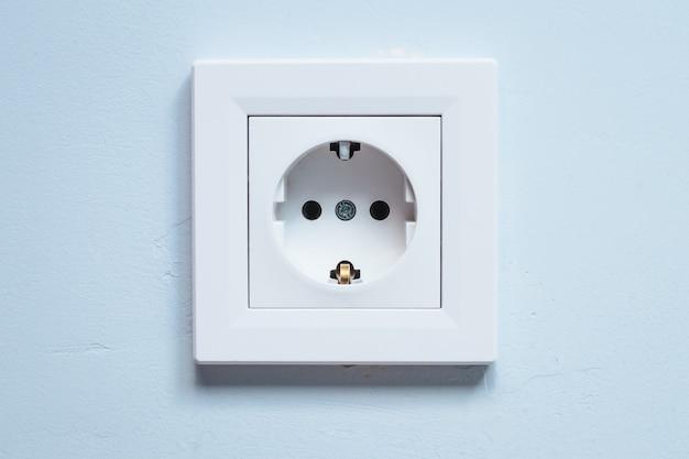 Белая розетка с заземляющими контактами на синей стене. концепция потребления электроэнергии.
