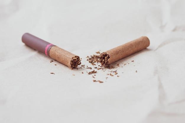 Сломанные темные сигары на фоне нейтральной бумаги. концепция здорового образа жизни. сокрушенная сигарета и рассеянный табак. копировать, текстовое пространство. вредная привычка, никотиновая зависимость. всемирный день без табака.