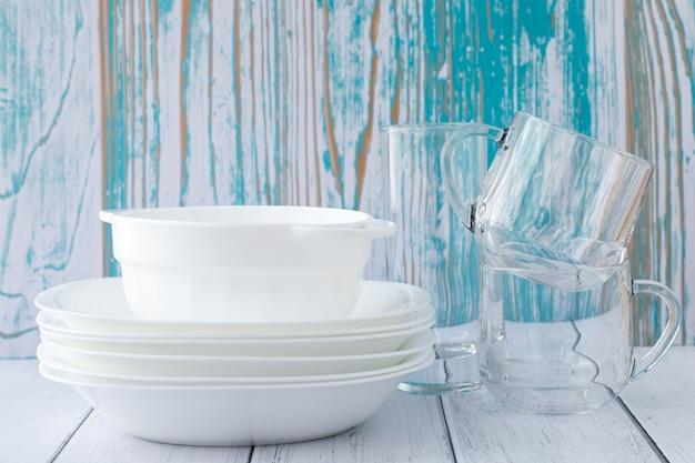 テーブルの上の白いボウル、グラス、プレート。きれいな料理のスタック