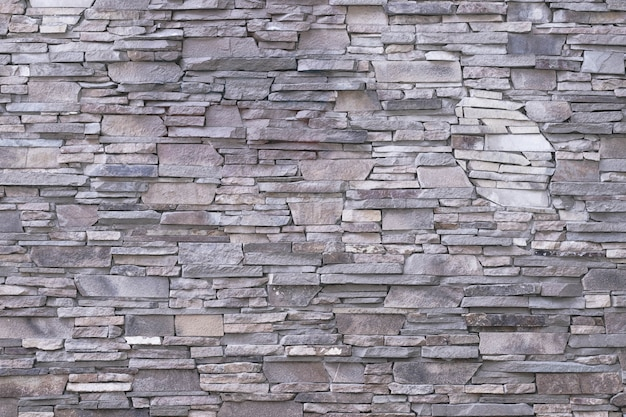 Серая предпосылка каменной стены.