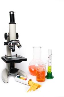 白い背景の上の顕微鏡と実験用ガラス器具