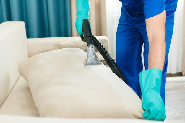 Сотрудник клининговой компании предоставляет услуги химической и паровой очистки дивана. паровой очиститель