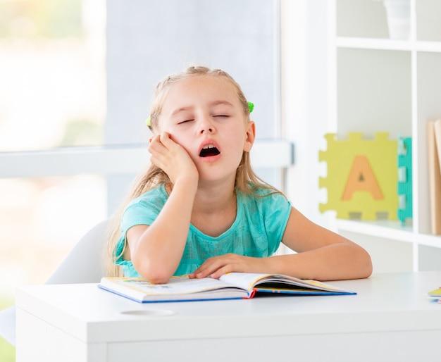 Милая мечтательная маленькая девочка в школе