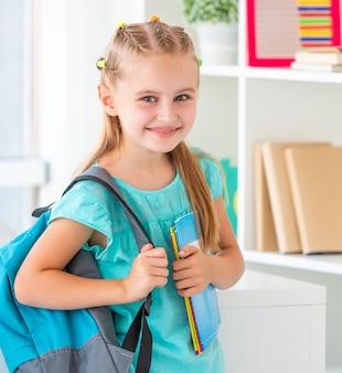 Улыбающаяся маленькая девочка готова вернуться в школу