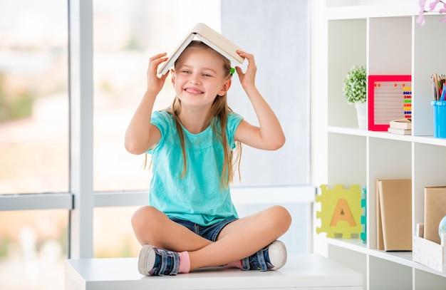 Девочка играет с учебником