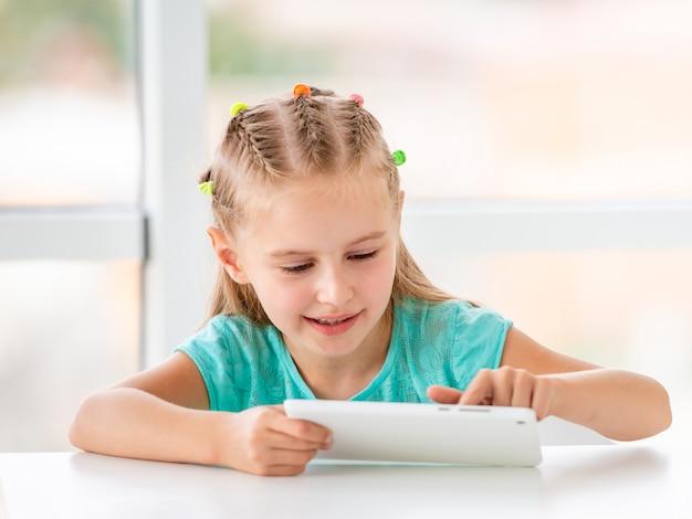 Счастливая маленькая девочка играет с телефоном
