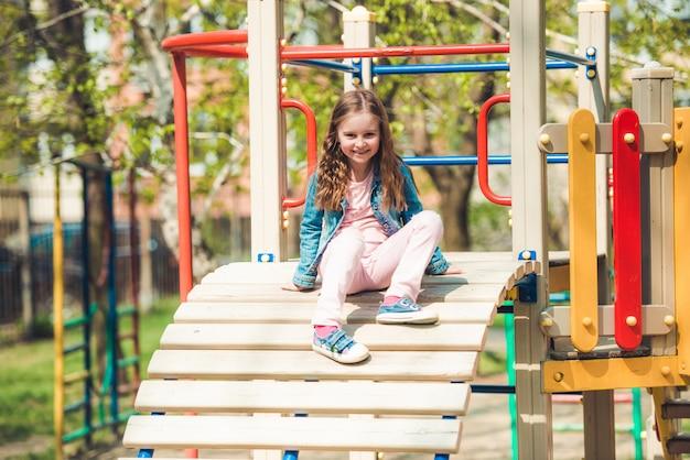 小さな女の子が遊び場のはしごで遊んで
