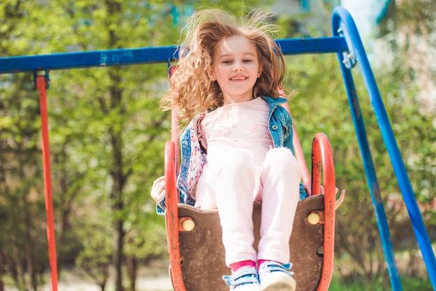 公園のブランコに乗っている小さな子供