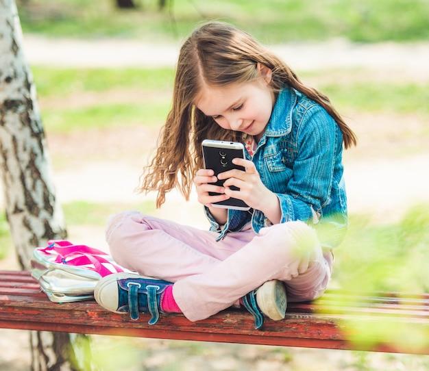 Маленькая девочка сидит с ее телефоном в парке