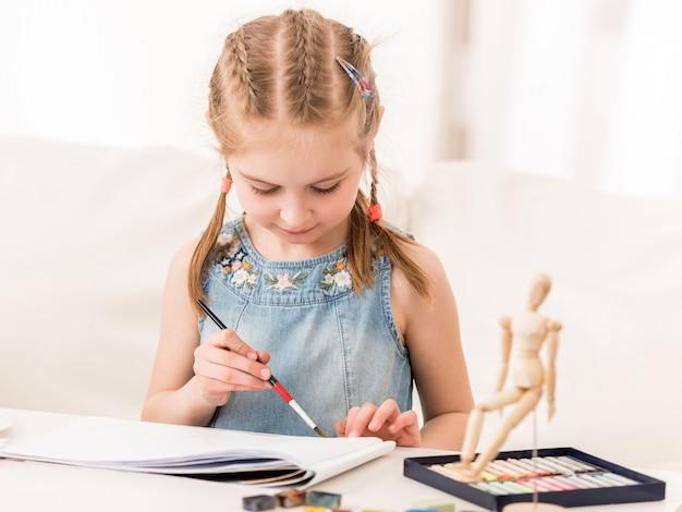 Маленькая девочка рисует акварелью