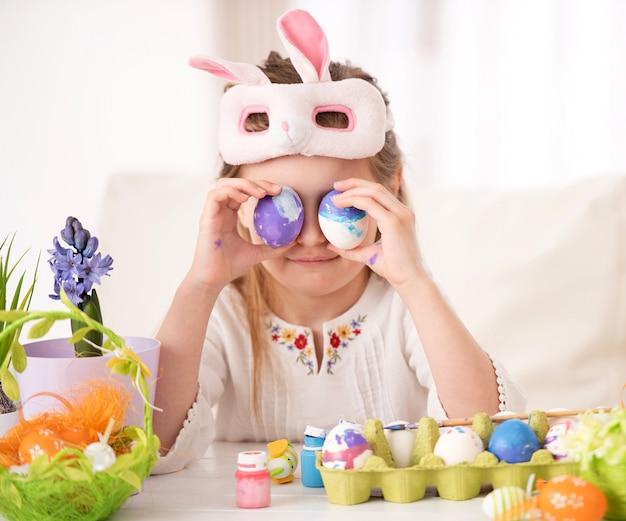 Девочка играет с коллекцией пасхальных яиц