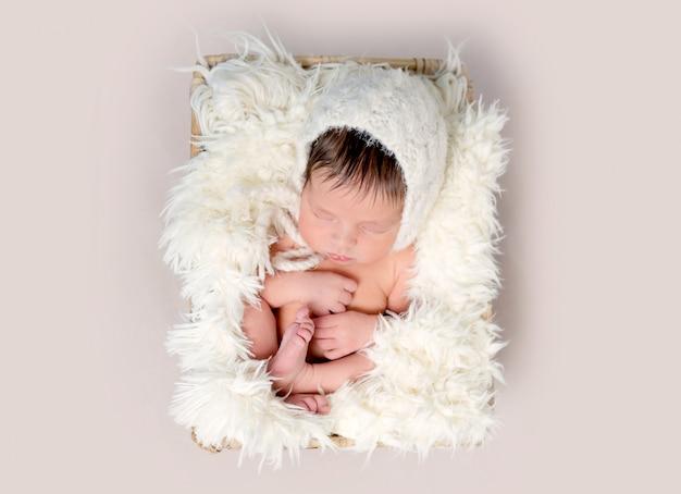 Новорожденный ребенок спит на спине, свернувшись ногами