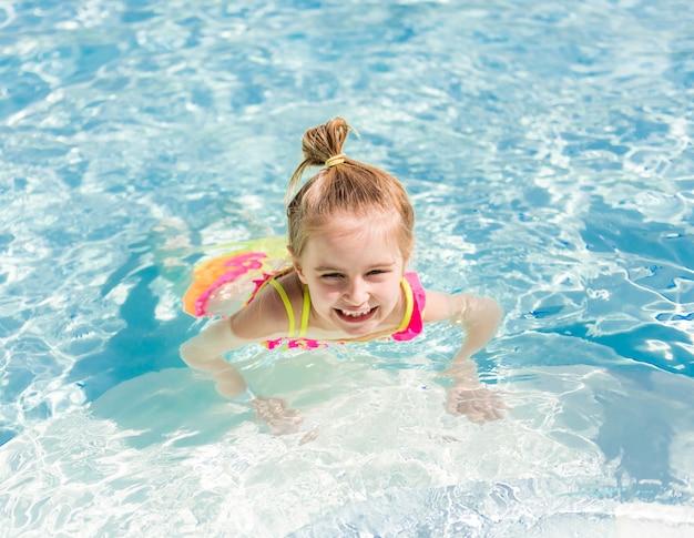 笑顔の女の子がプールサイドに泳ぎます