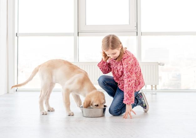 Милая девушка кормит собаку
