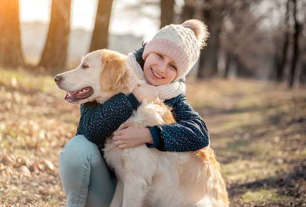 Улыбающаяся девушка обнимает милый пес