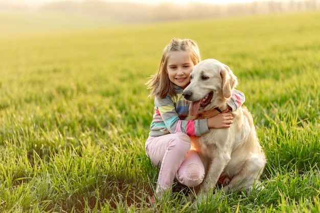 Маленькая девочка обнимает красивую собаку