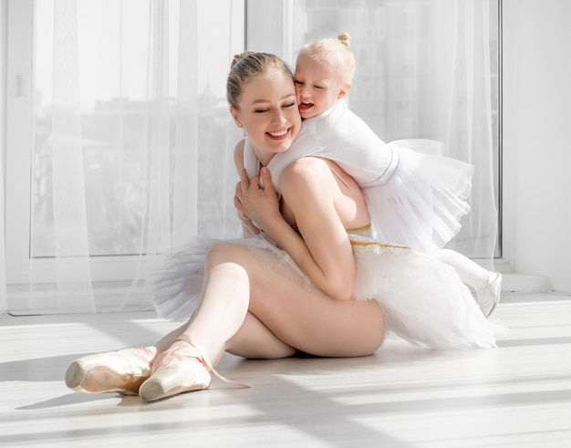 若い母親がバレエスタジオで少し笑顔の娘を抱いて