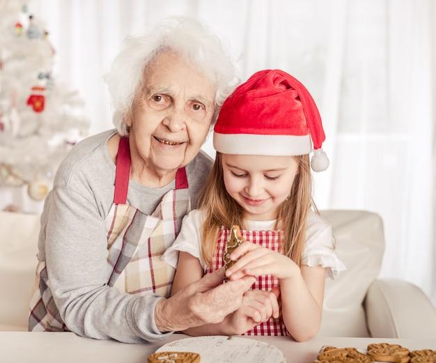 Бабушка с внучкой держит печеное печенье