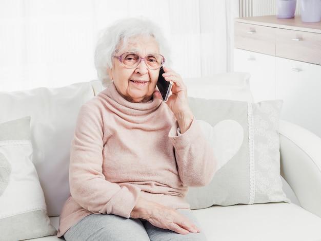 Старая женщина разговаривает по телефону