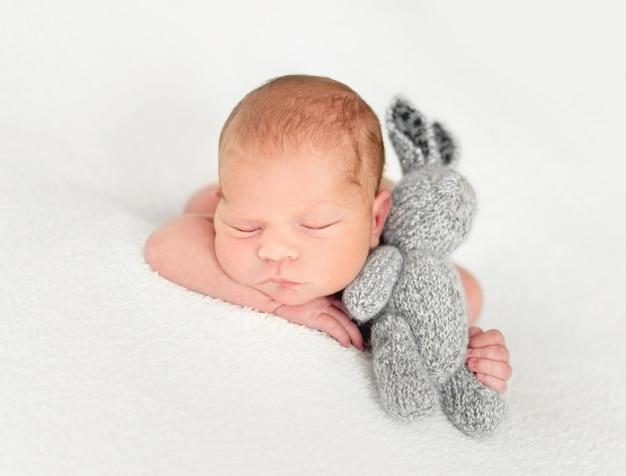 Маленький ребенок лежит с игрушкой зайца