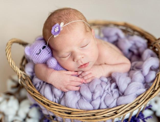 Спокойный сонный новорожденный с игрушкой