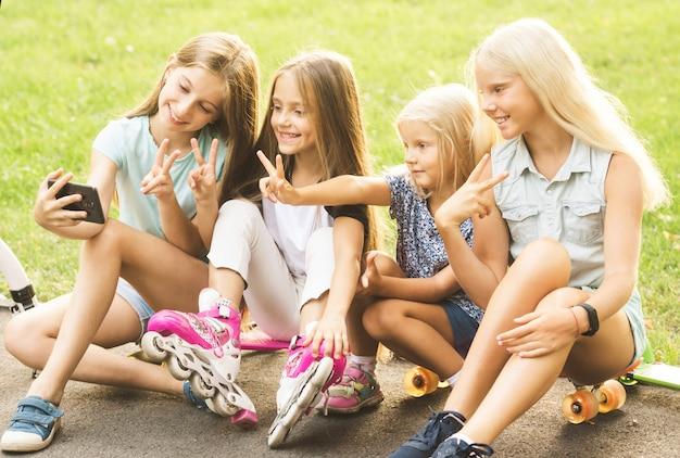 Маленькие девочки, принимающие селфи на открытом воздухе