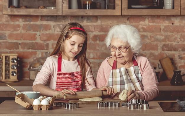 Пожилая женщина учит маленькую девочку готовить домашнее печенье