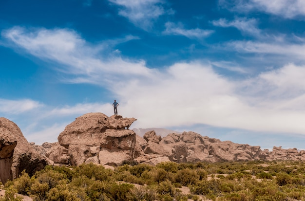 ボリビアの岩が多い丘の端に立っている人