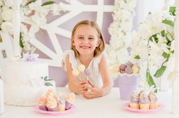 Маленькая улыбающаяся белокурая девушка, держащая красочные сладкие леденцы на палочке на фоне симпатичного шоколадного батончика
